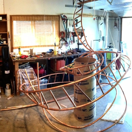 We bent the coils into shape using iron bars for leverage and drilled holes for the rungs on a drill press. Here, it is suspended from ceiling to keep it from collapsing. Concrete pouring tube in center of sculpture to gauge how the ladder would relate to wrapping around column.