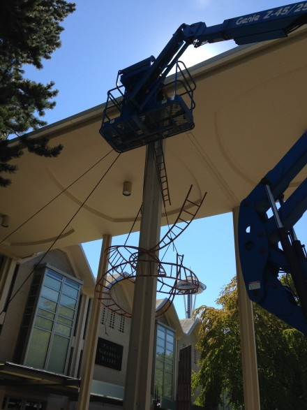 Riggers using crane to add stainless steel stabilizer cable and to suspend final 12' stretch of ladder from rooftop and attach it to rest of sculpture